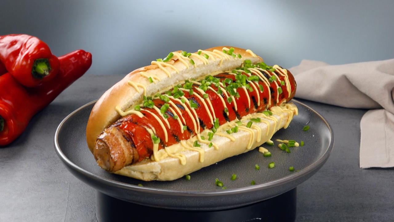 Hotdog mit grober Bratwurst in Bacon eingewickelt