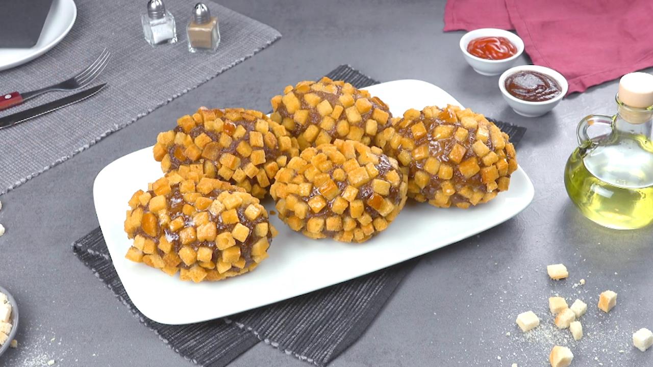 5 Kartoffen in einem Hackfleisch-Mantel und einer frittierten Croûtons-Kruste auf einem Teller serviert