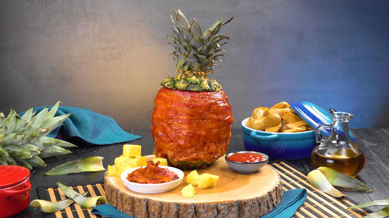 Marinierte Hähnchenbrust in mit Bacon umwickelter Ananas gegrillt