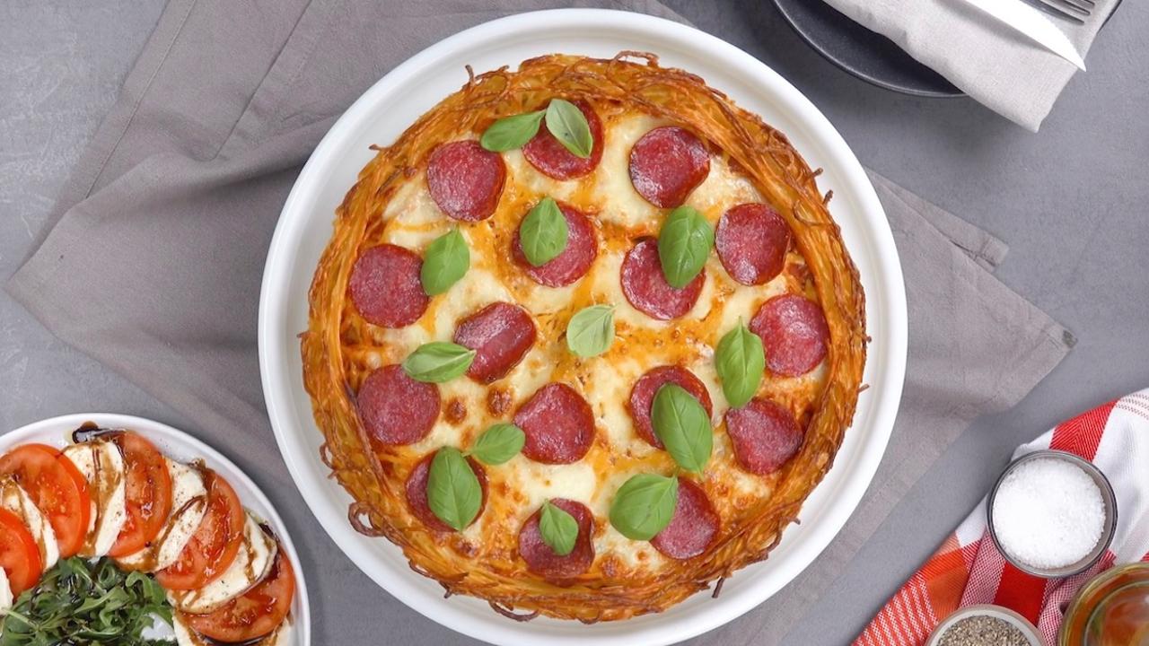 Pizza aus Spaghetti, gefüllt mit Bolognese und belegt mit Salami, Mozzarella und Cheddar