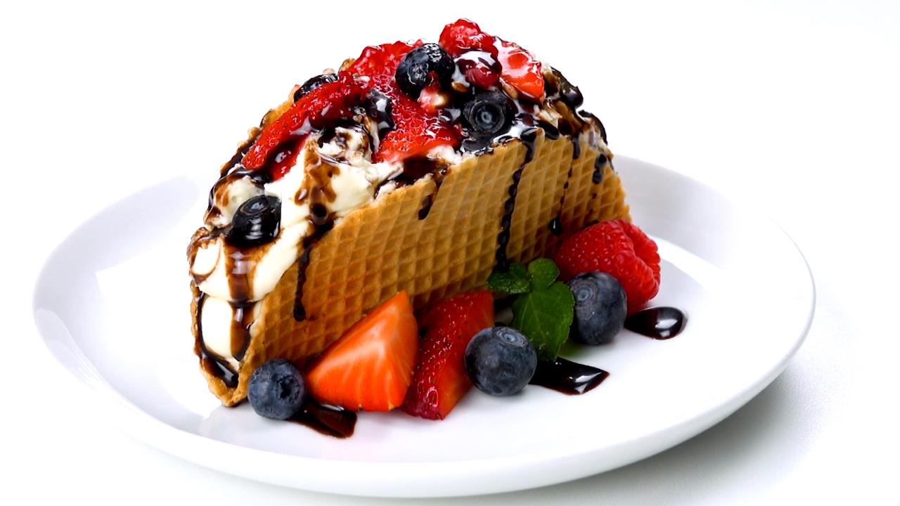 Eine Eiswaffel, die aussieht wie ein Taco, der mit einer weißen Creme, Beeren und Schokosße gefüllt ist
