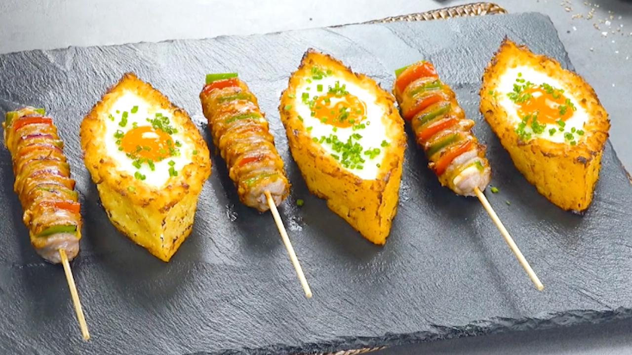 Kartoffel Boote mit Ei und Hasselback Bratwurst am Stiel serviert auf einer Steinplatte